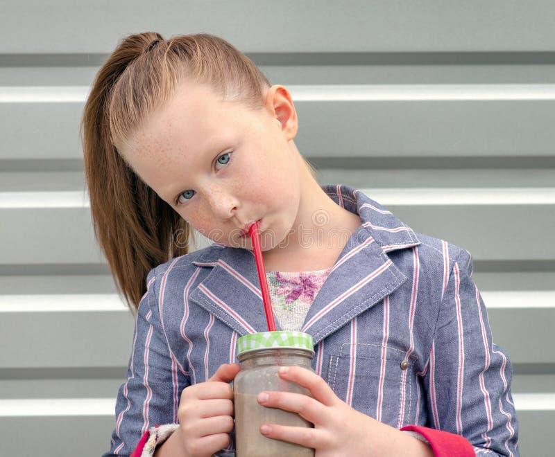 Smoothie potable de lait chocolaté de petite fille photo stock