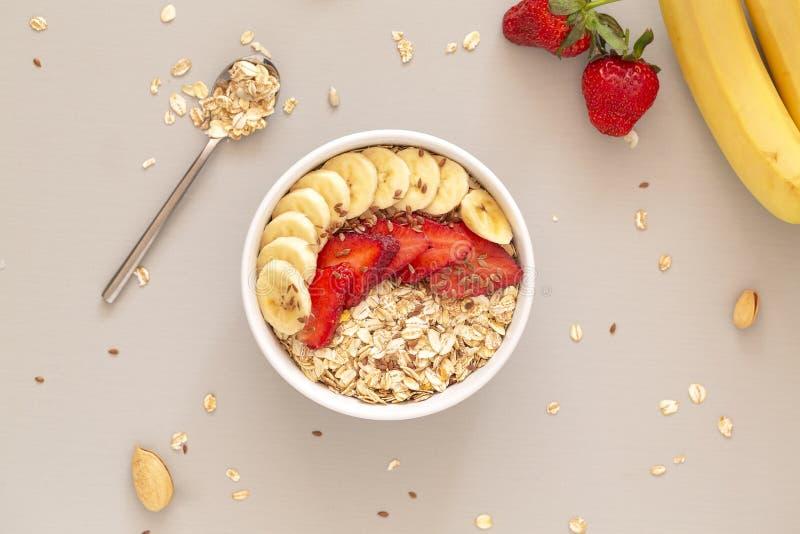Smoothie puchar z muesli, truskawkami, banan?w plasterkami i lna ziarnem, poj?cia zdrowe jedzenie Mieszkanie nieatutowy zdjęcie royalty free
