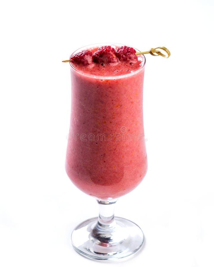 Smoothie rose dans un verre décoré des baies de framboise sur le fond blanc photographie stock