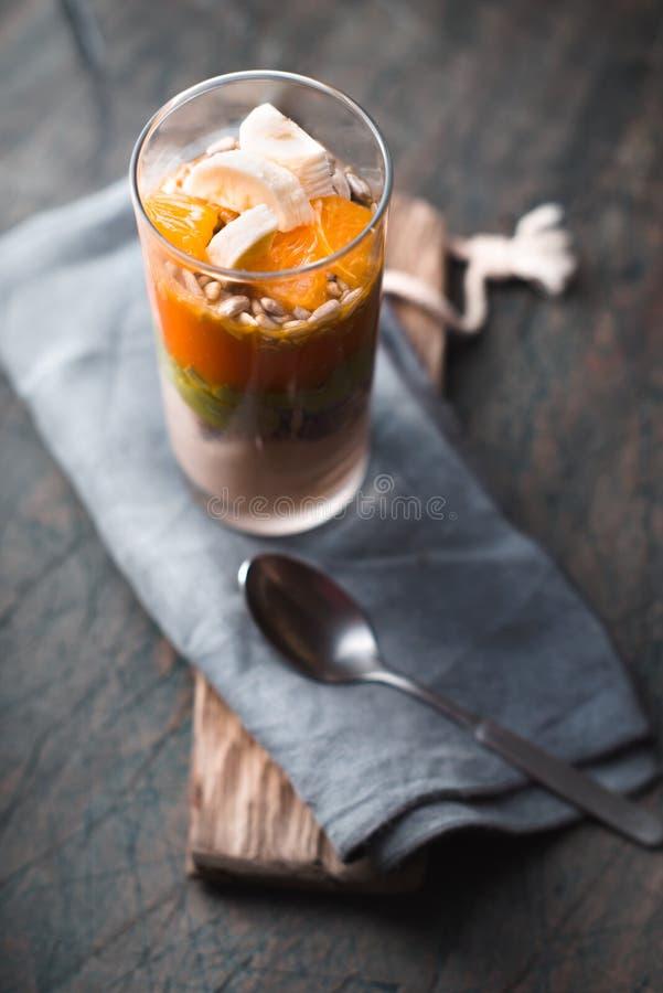 Smoothie sain avec la banane, le pampkin, l'avocat et les graines de lin dans bouteilles en verre sur un fond rustique photographie stock