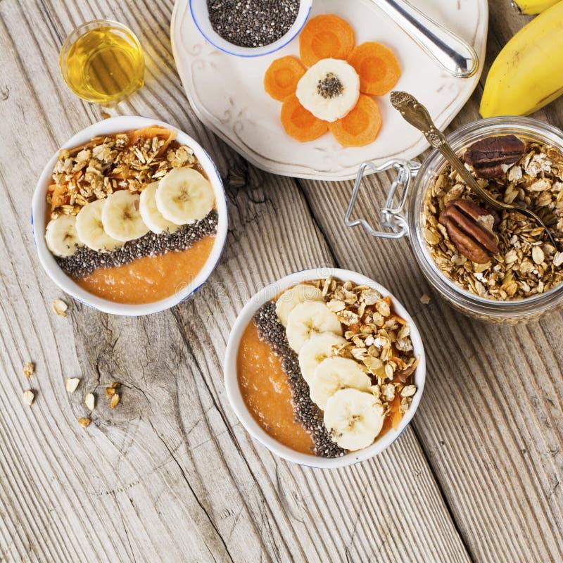Smoothie sain de banane de carotte de petit déjeuner avec des graines de granola et de chia photographie stock