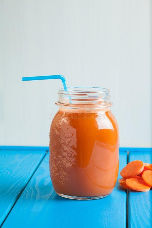 Smoothie sain de carotte dans un pot sur le fond en bois bleu image stock
