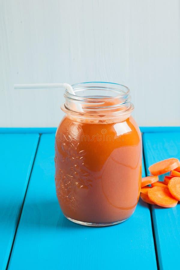 Smoothie sain de pomme de carotte dans un pot sur le fond en bois bleu images stock