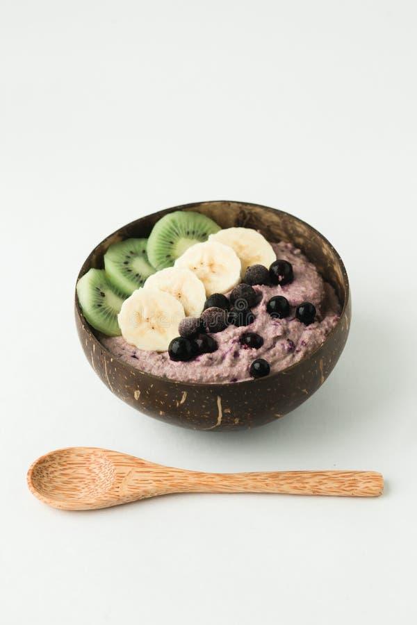 Smoothie sano con las frutas, la placa hecha de cáscara del coco y la cuchara de madera imágenes de archivo libres de regalías