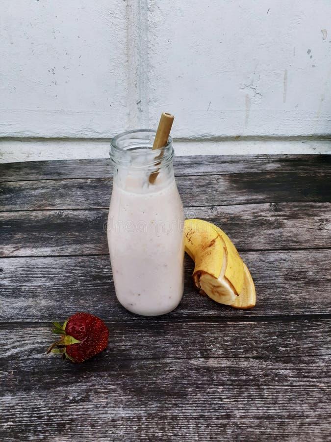 Smoothie sano de la comida hecho de la fresa y de la leche del plátano en una botella de cristal con una paja de bambú en un fond foto de archivo