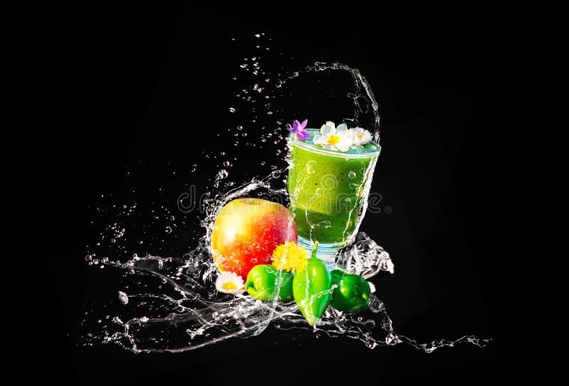 Smoothie verde, flores comestibles y frutas, chapoteo del agua imágenes de archivo libres de regalías