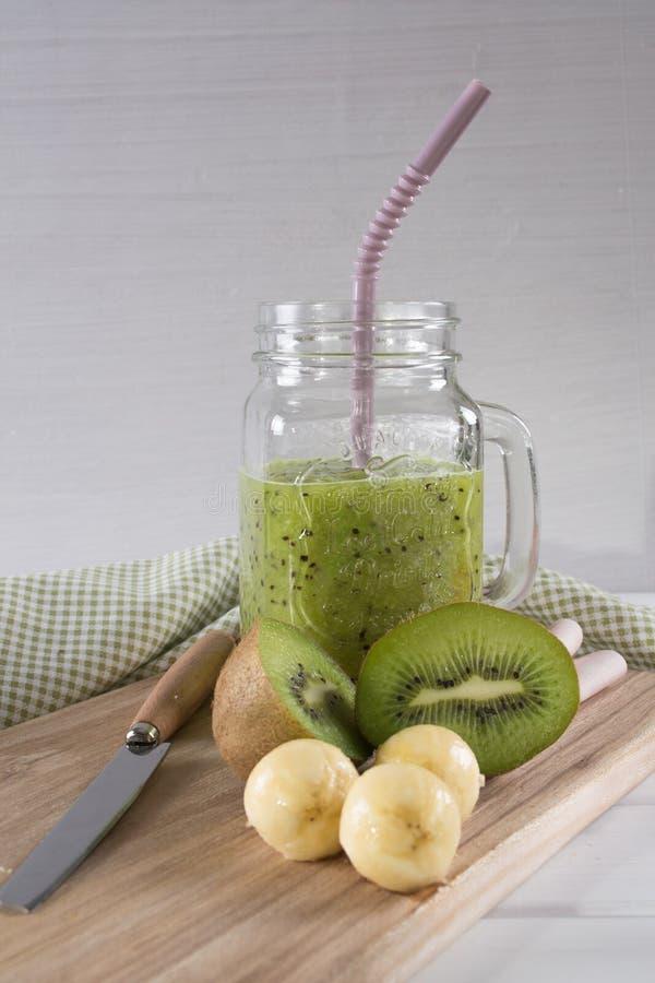Smoothie verde fresco y sano del jugo con el kiwi y el plátano en el tarro de cristal imagenes de archivo