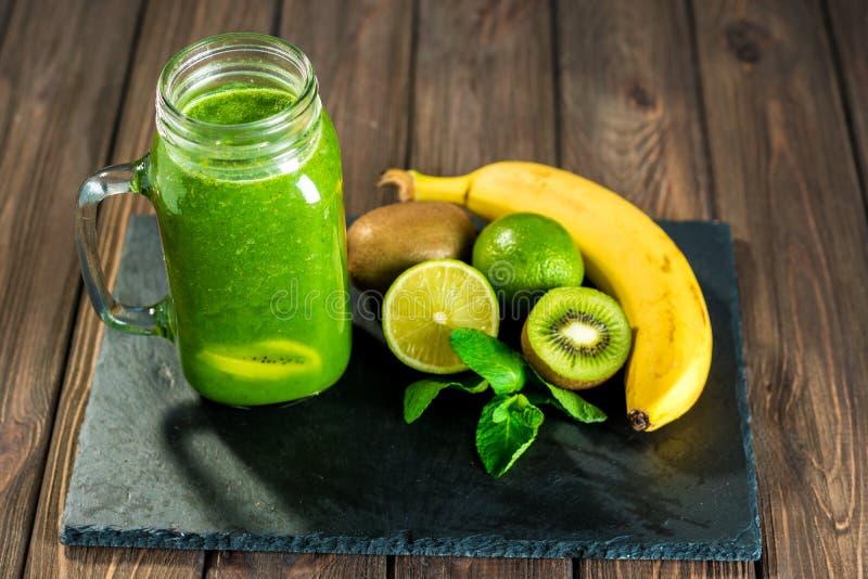 Smoothie verde mezclado con los ingredientes en el tabl de madera de piedra fotografía de archivo