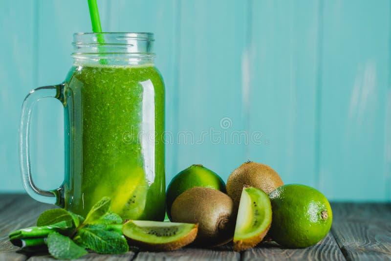 Smoothie verde mezclado con los ingredientes en selectiv de madera de la tabla foto de archivo libre de regalías