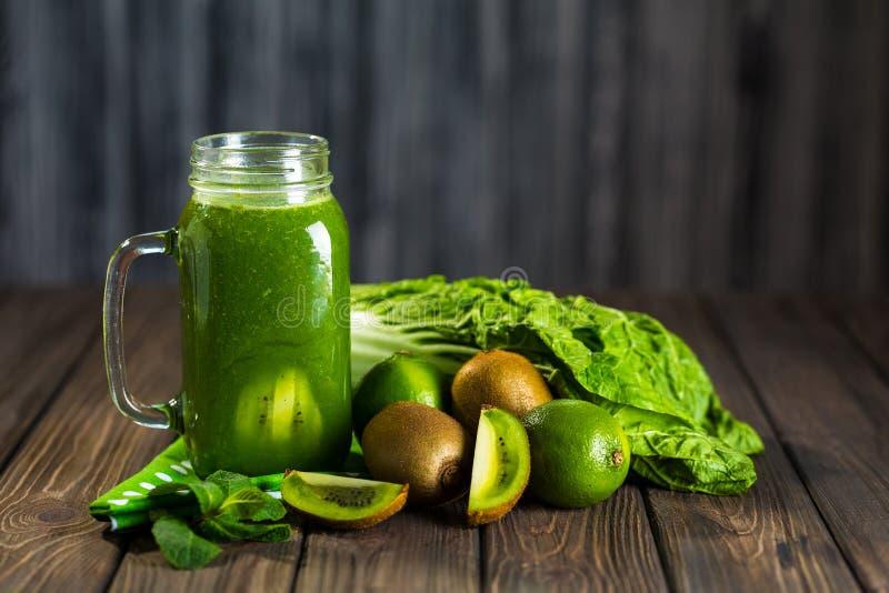 Smoothie verde mezclado con los ingredientes en selectiv de madera de la tabla imágenes de archivo libres de regalías