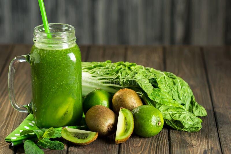 Smoothie verde mezclado con los ingredientes en selectiv de madera de la tabla fotografía de archivo