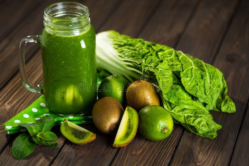 Smoothie verde mezclado con los ingredientes en selectiv de madera de la tabla foto de archivo