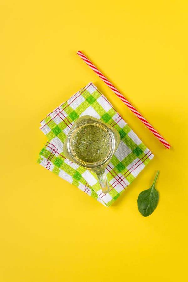 Smoothie verde recién preparado en fondo amarillo foto de archivo