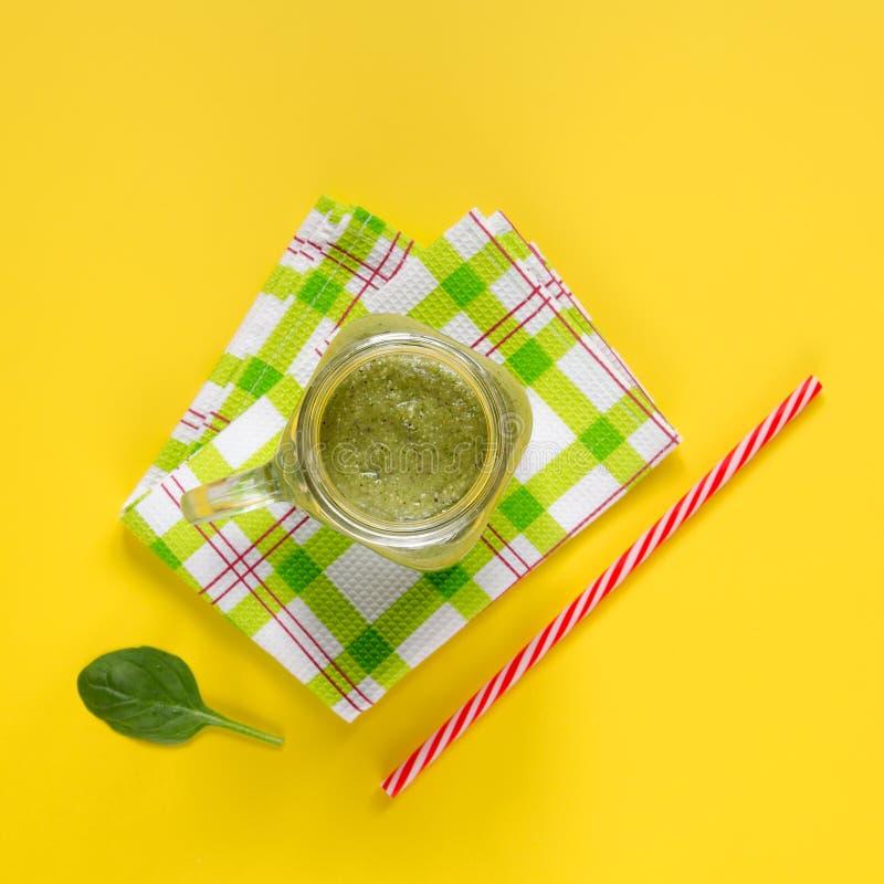 Smoothie verde recién preparado en fondo amarillo fotografía de archivo