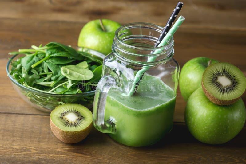 Smoothie verde recientemente mezclado de la fruta en el tarro de cristal con la paja Verde Apple Kiwi Detox Healthy Food Toned de foto de archivo