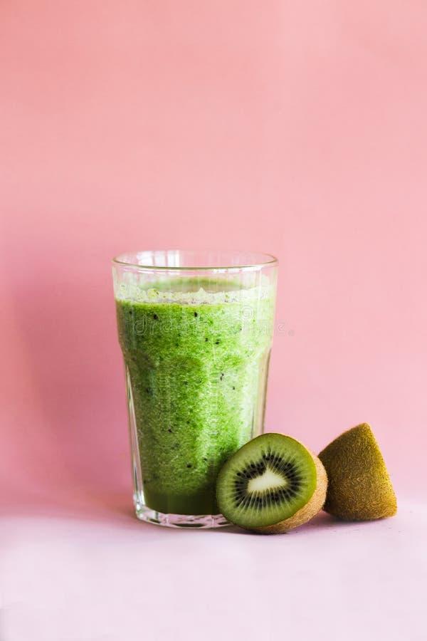Smoothie verde sano con el kiwi en una taza de cristal en un fondo rosado fotografía de archivo