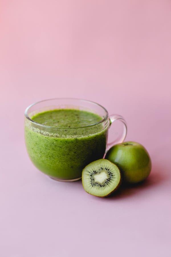 Smoothie verde sano con el kiwi y manzana en una taza de cristal en fondo rosado fotos de archivo