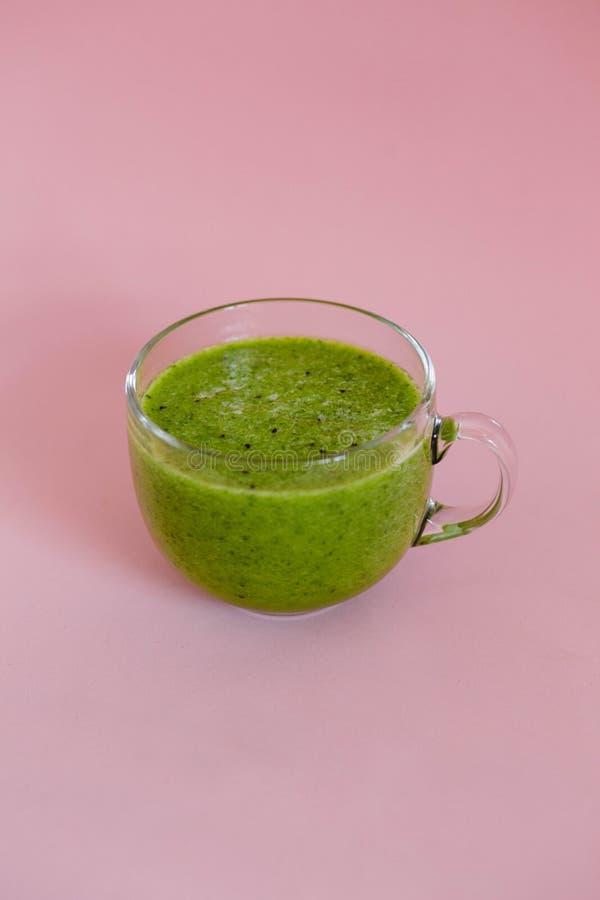 Smoothie verde sano con el kiwi y manzana en una taza de cristal en fondo rosado imágenes de archivo libres de regalías
