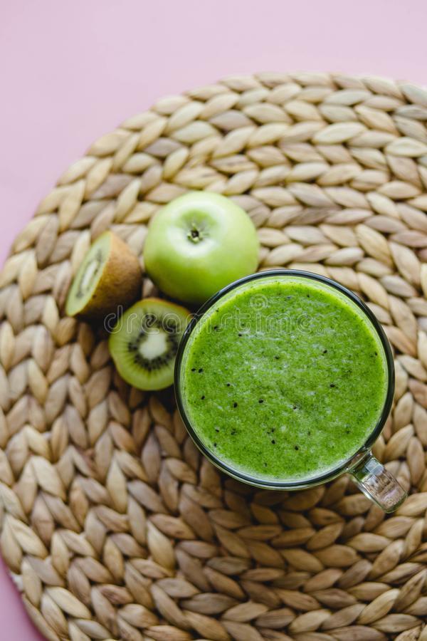 Smoothie verde sano con el kiwi y manzana en una taza de cristal en fondo rosado fotografía de archivo libre de regalías