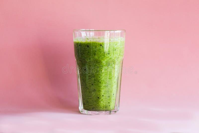 Smoothie verde sano con en una taza de cristal en un fondo rosado imágenes de archivo libres de regalías