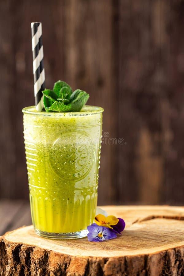 Smoothie vert emballé avec les ingrédients sains décorés des feuilles et des fleurs vertes photos stock