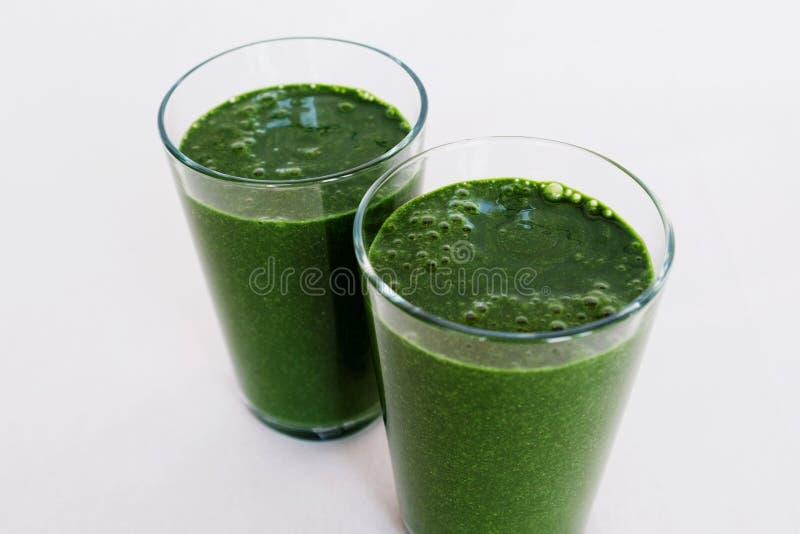 Smoothie vert frais avec les feuilles de chou frisé, la banane, le lait de noix de coco, le spirulina et les graines de lin sur l photo libre de droits