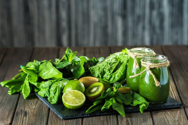 Smoothie vert mélangé avec des ingrédients sur le conseil en pierre, table en bois images libres de droits