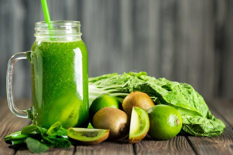 Smoothie vert mélangé avec des ingrédients sur le selectiv en bois de table photo stock