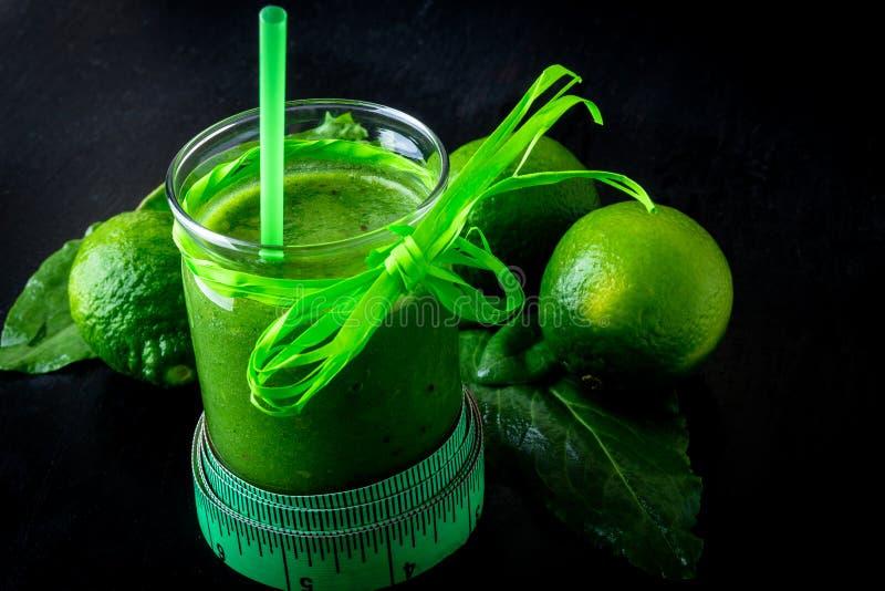 Smoothie vert près de centimètre et ingrédients pour lui sur le fond en bois noir Régime detox Boisson saine Nourriture claire photographie stock