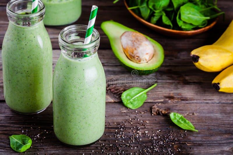 Smoothie vert sain avec des graines de banane, d'épinards, d'avocat et de chia dans des bouteilles en verre images libres de droits