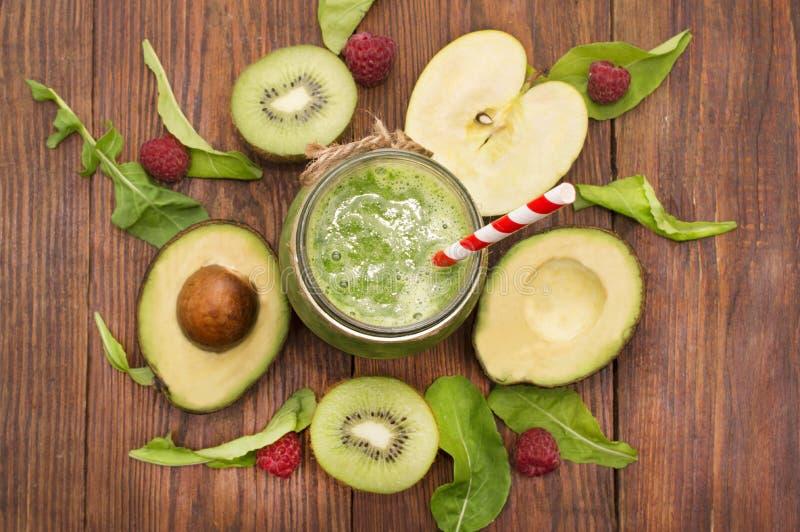 Smoothie vert sain avec la banane, les épinards, l'avocat et le kiwi dans bouteilles en verre sur un rustique photos stock