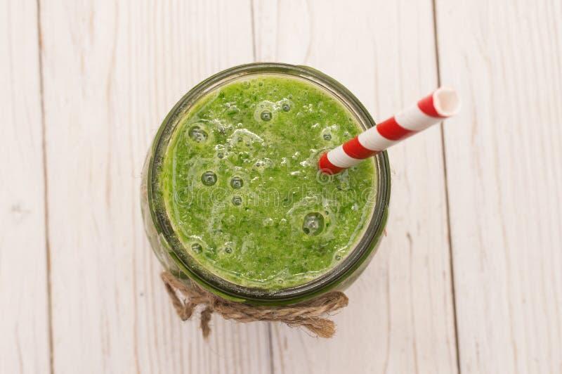Smoothie vert sain avec la banane, les épinards, l'avocat et le kiwi dans bouteilles en verre sur un rustique image libre de droits