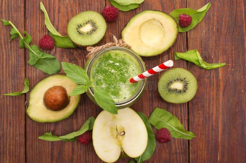 Smoothie vert sain avec la banane, les épinards, l'avocat et le kiwi dans bouteilles en verre sur un rustique photos libres de droits