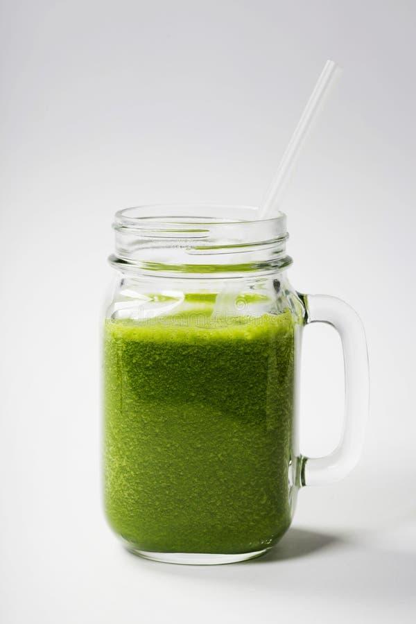 Smoothie vert sain avec la paille dans une tasse de pot image stock