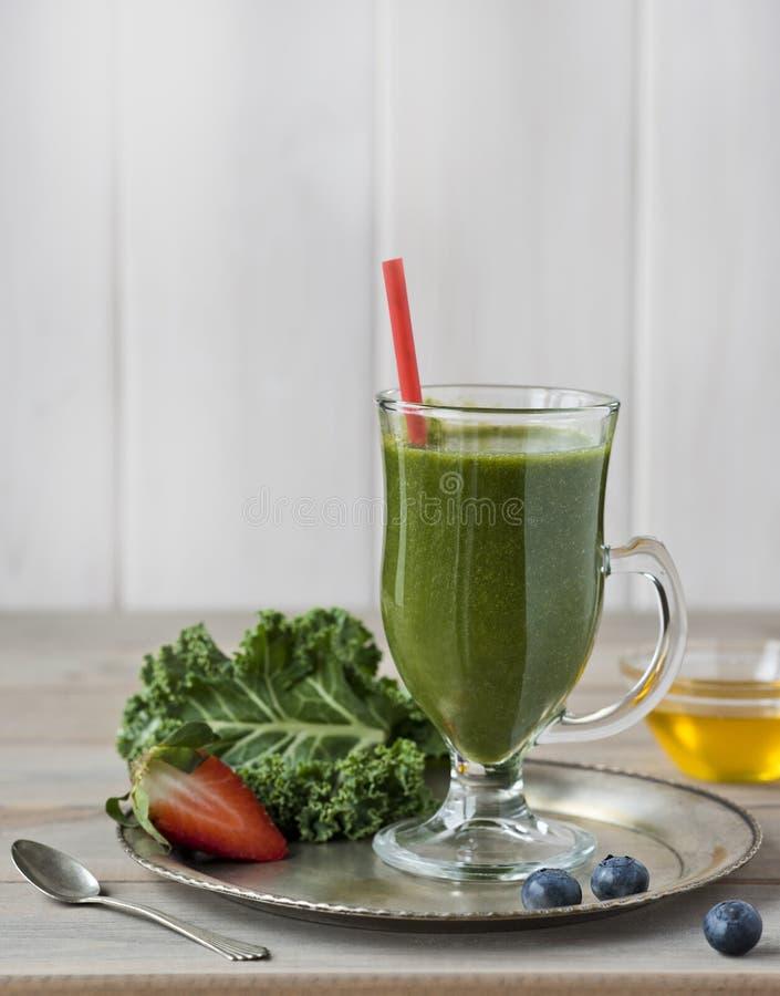 Smoothie vert sain avec le chou frisé, les fraises, les myrtilles et le miel dans la bouteille avec le label sur le fond en bois  images libres de droits