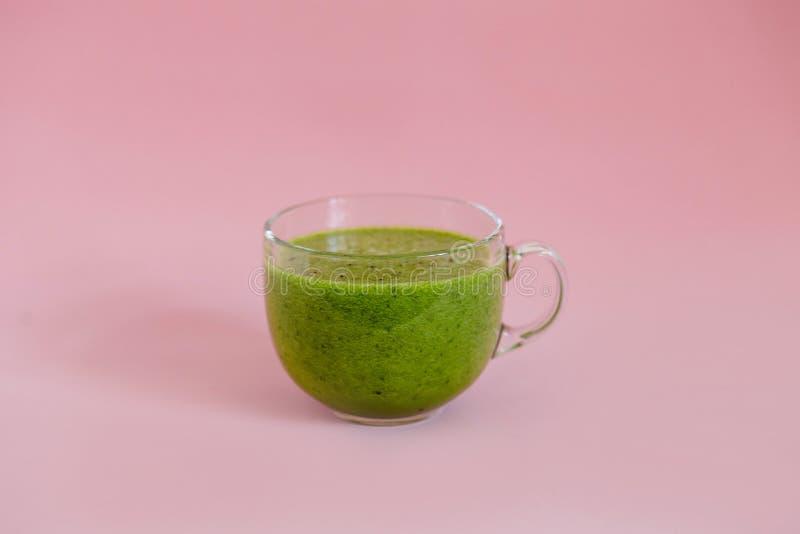 Smoothie vert sain avec le kiwi et pomme dans une tasse en verre sur le fond rose photographie stock libre de droits