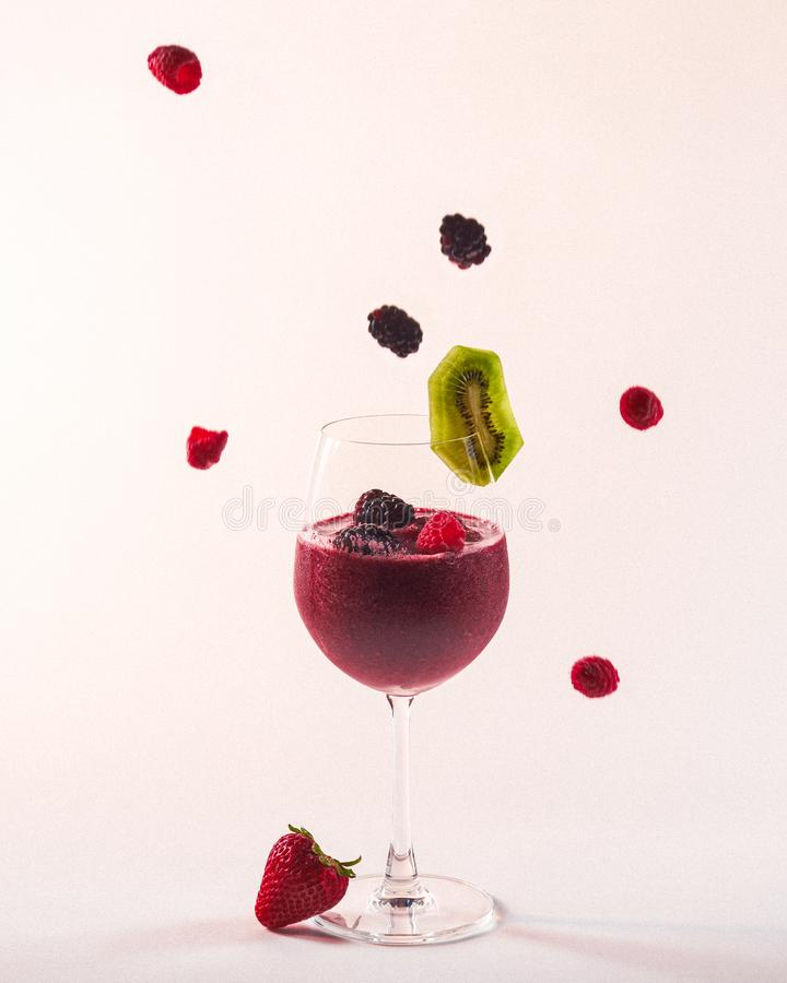 Wine Glass Smoothie with Falling Fruit royalty free stock image