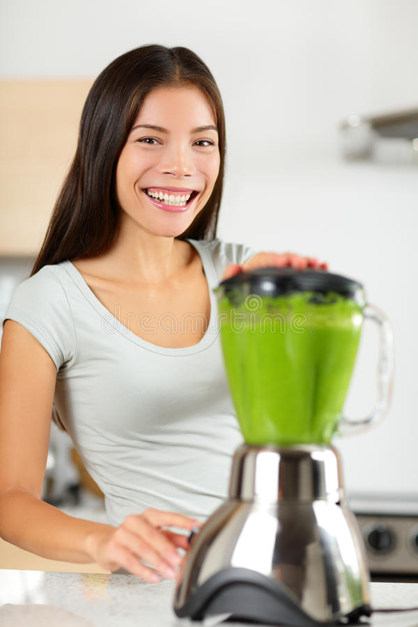 Smoothie woman making vegetable green smoothies. With blender home in kitchen. Healthy eating lifestyle concept portrait of beautiful young woman preparing stock photo