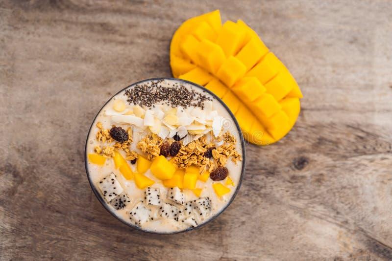Smoothiebunkar som göras med mango, bananen, granola, den grated kokosnöten, drakefrukt, chiafrö och mintkaramellen på träbakgrun arkivbilder