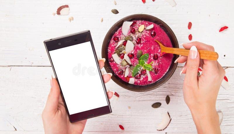 Smoothiebunke med den moderna mobiltelefonen arkivbild