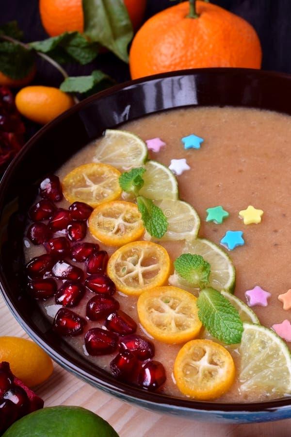 Smoothiebunke som garneras med kumquats, granatäpplet, limefrukt och mintkaramellen royaltyfria foton