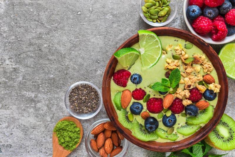 Smoothiebunken som göras av grönt te för matcha med nya frukter, bär, muttrar, frö med en sked för sunt, bantar frukosten arkivbild