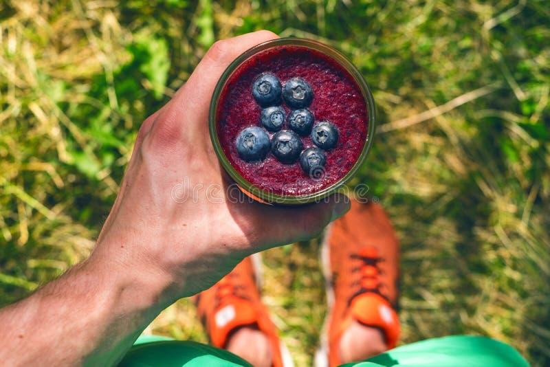 Smoothiegetränk ein Sportmann in einer Natur Gläser von Smoothie mit Beere und Minze Beere, Blatt und Kalk, raspberriesFruit Heal stockfoto