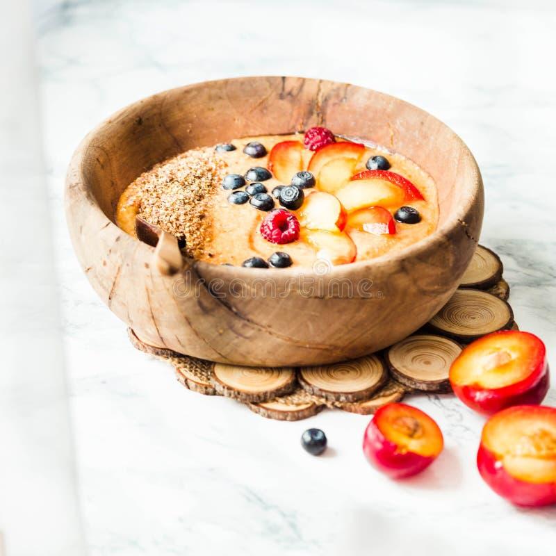 Smoothiekom met perziken, pruimen en bosbessen in houten Di royalty-vrije stock afbeelding