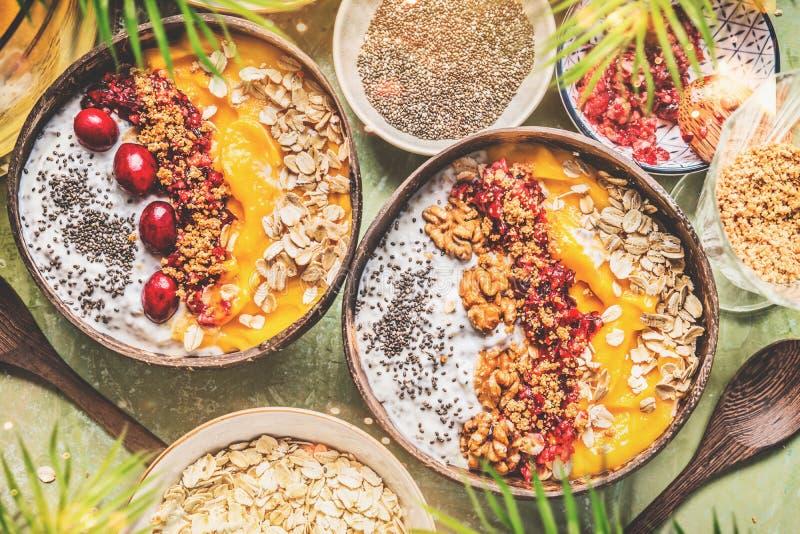Smoothiemangoschüsseln mit chia Samen-Jogurtpudding und Moosbeeren, Nüsse, Hafermehl, das in den Kokosschalen mit Löffel, Draufsi stockfotografie