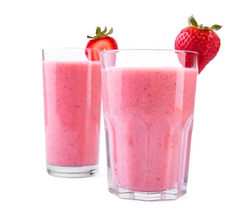 Smoothien från jordgubbar och mjölkar med ett bär på en överkant av exponeringsglas på vit bakgrund Exponeringsglas av den söta s arkivfoton