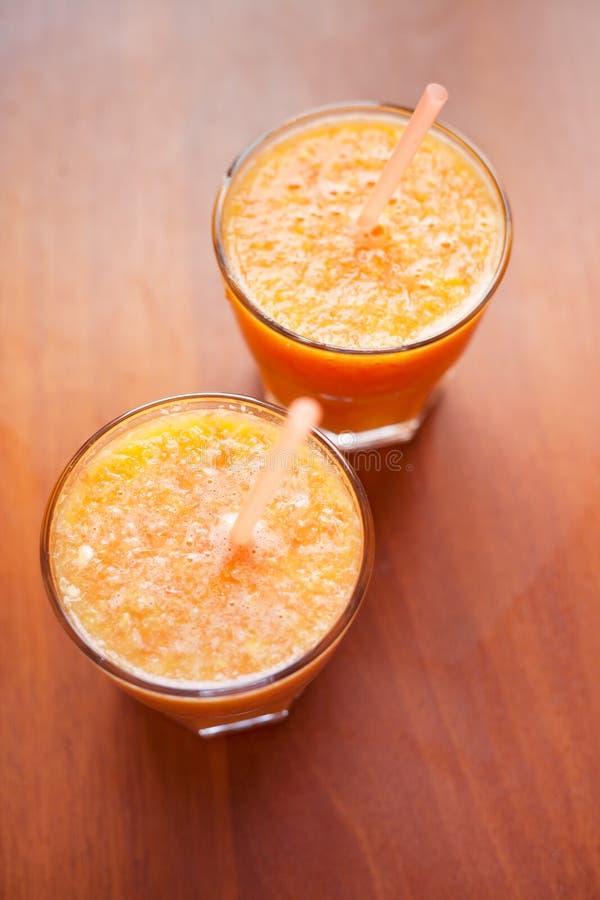 Smoothies лимона и апельсина на таблице с кусками лимона и апельсина в чашках стекла с трубками стоковые изображения