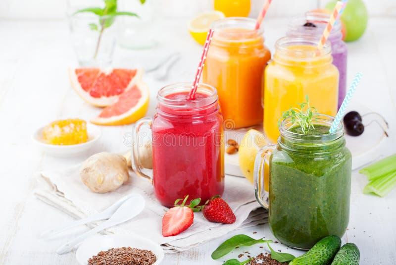 Smoothies, соки, напитки, разнообразие пить с свежими фруктами и ягоды на белой деревянной предпосылке стоковая фотография