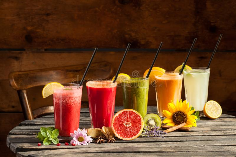 Smoothies assortis de fruit sur le fond en bois images stock