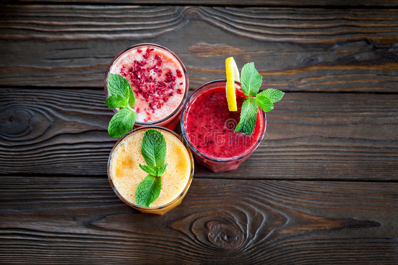 Smoothies assortis de fruit sur une table en bois image stock